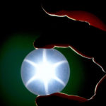Photograph of a spherical star quartz (G3125) from the National Gem Collection held between two fingers