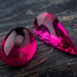 Rubellite gemstone jewelry photo with black stone and dark lighting.